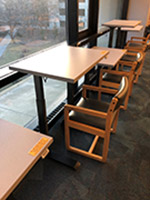 Row of adjustable-height tables with chairs on third floor of Parks Library