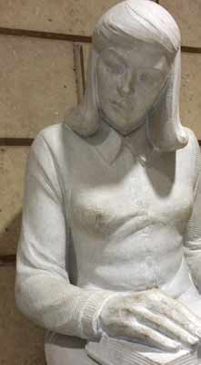 Sculpture of girl glancing slightly toward boy
