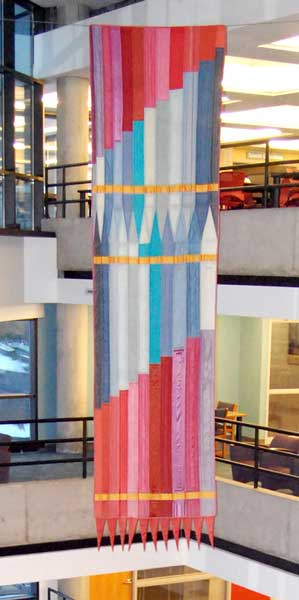 Long pieced fabric banner hung in atrium of Parks, reds at top and bottom, blues in middle