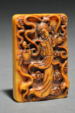 17 - Pendant Plaque, Woman - orangish color, woman is something with a handle, surrounded by wavy forms
