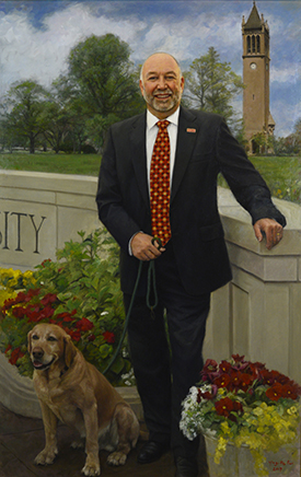 Steven Leath with his dog, Campanile in the background near the Iowa State University Wall