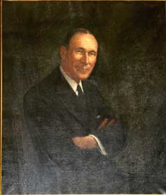 Portrait of Raymond Hughes, arms folded, looking at us and smilling