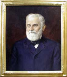 Shows Welch with white hair and beard, blue suit